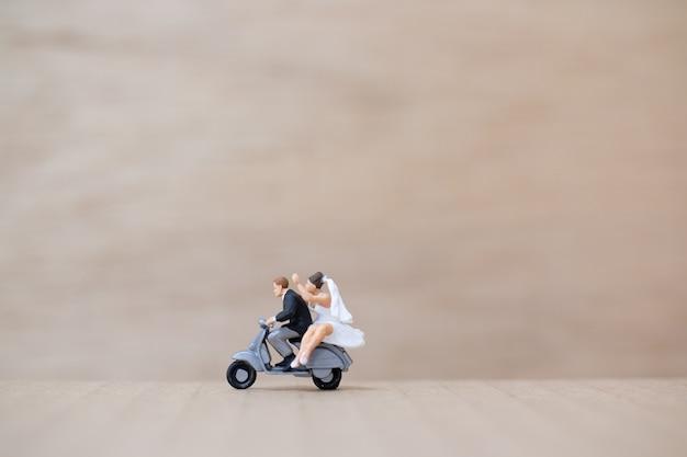 Miniatuurmensen: bruid en bruidegom op houten achtergrond