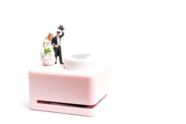 Miniatuurmensen, bruid en bruidegom staan met hartvormige ponsmachine