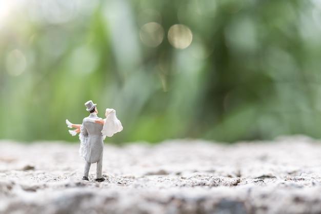 Miniatuurmensen: bruid en bruidegompaar die zich openlucht bevinden
