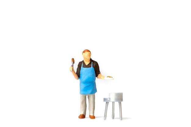 Miniatuurmensen, chef-kok die lapje vlees op barbecuegrill koken die op witte achtergrond wordt geïsoleerd