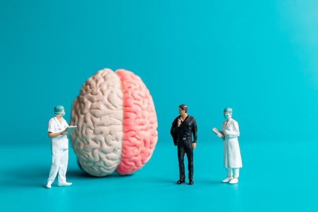 Miniatuurmensen chirurg sprak met patiënt over hersenletsel. wereld beroerte dag concept.
