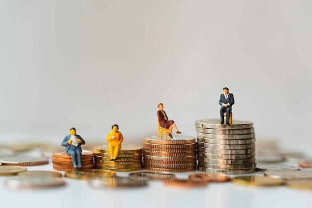 Miniatuurmensen, commerciële teamzitting op stapelmuntstukken die als bedrijfsgroepswerk en financieel concept gebruiken