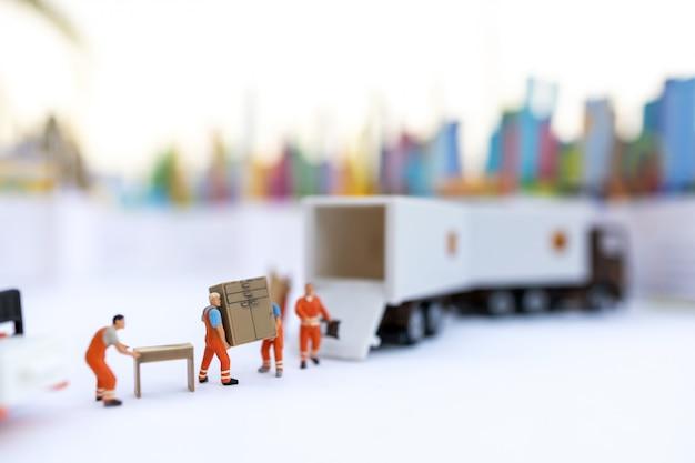 Miniatuurmensen: de bezorgservice van een lader. concepten van logistiek en transport