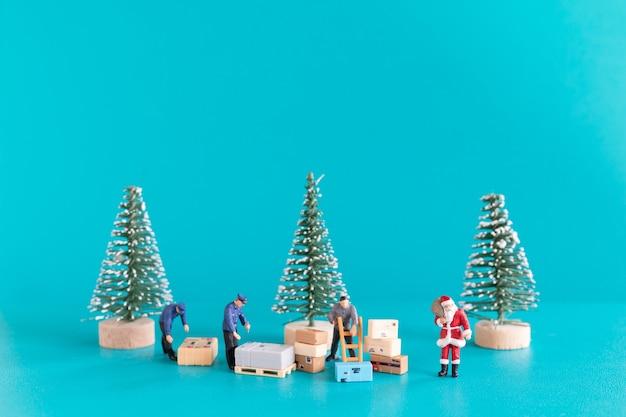 Miniatuurmensen, de kerstman en zijn arbeidersteam bereiden zich voor op de jaarlijkse kerstavondlevering van geschenken, kerstmis en een gelukkig nieuwjaarsconcept.