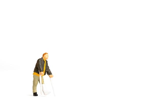 Miniatuurmensen, de volledige lengtemening van een mens met gebroken been gebruikt kruk op witte achtergrond.