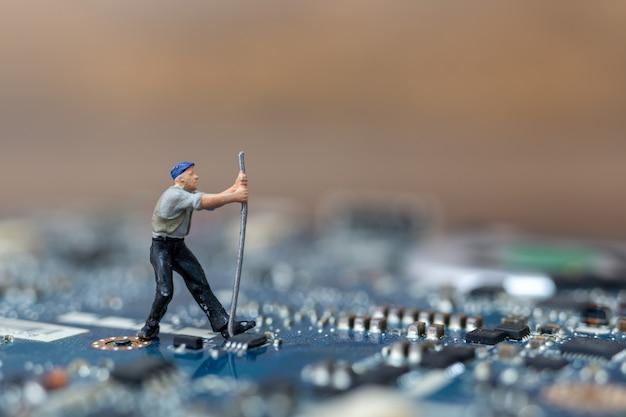 Miniatuurmensen die aan cpu-bord werken