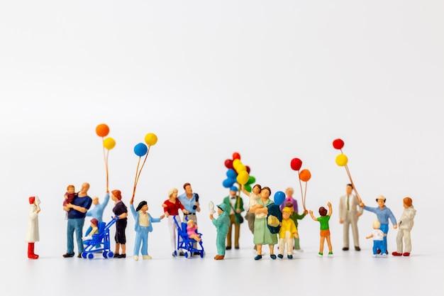Miniatuurmensen die ballon houden die op wit wordt geïsoleerd