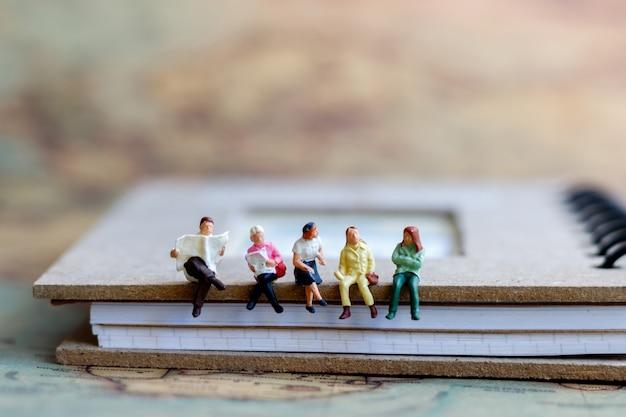 Miniatuurmensen die boek, concept onderwijs of de zaken lezen.