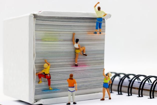 Miniatuurmensen die boek met uitdagende route op klip beklimmen.