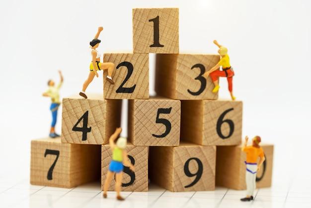 Miniatuurmensen die houten doos beklimmen met het bereiken van bovenkant. prestatie.