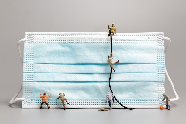 Miniatuurmensen die op het schone gezichtsmasker, gezondheidszorgconcept klimmen