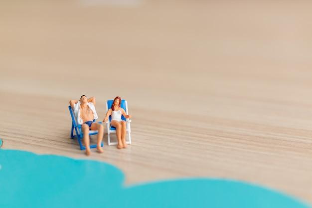 Miniatuurmensen die op het strand, het concept van de zomertijd zonnebaden Premium Foto