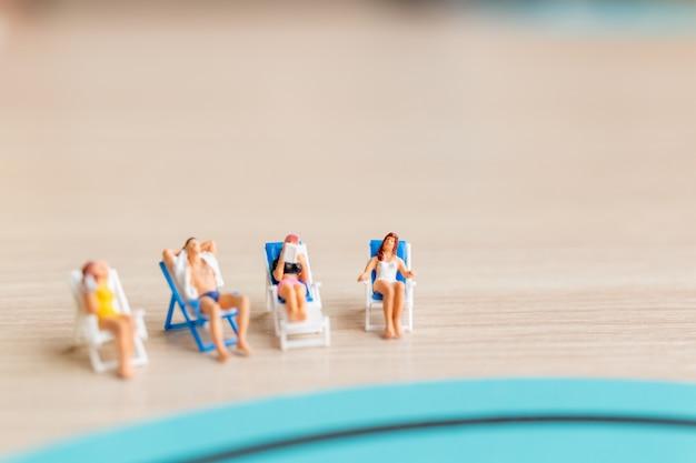 Miniatuurmensen die op het strand, het concept van de zomertijd zonnebaden
