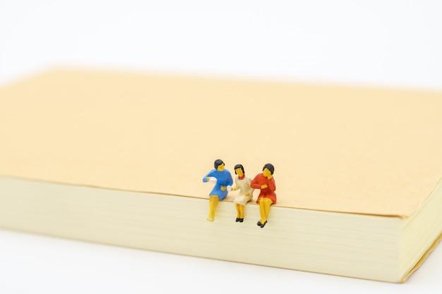 Miniatuurmensen die op notitieboekje zitten. bedrijfsconcept en teamwerk concept