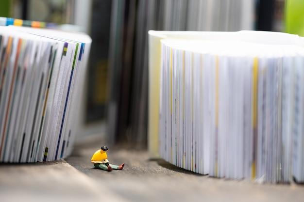 Miniatuurmensen die op notitieboekje zitten