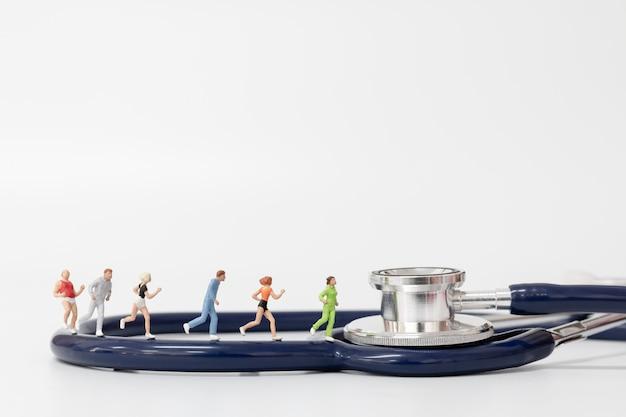 Miniatuurmensen die op stethoscoop lopen