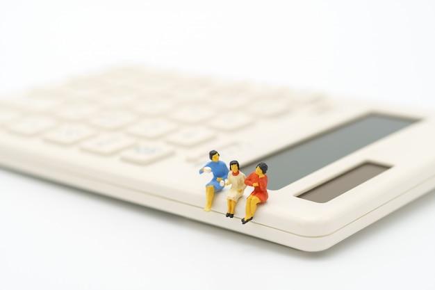 Miniatuurmensen die op witte calculator zitten. bedrijfsconcept en teamwork
