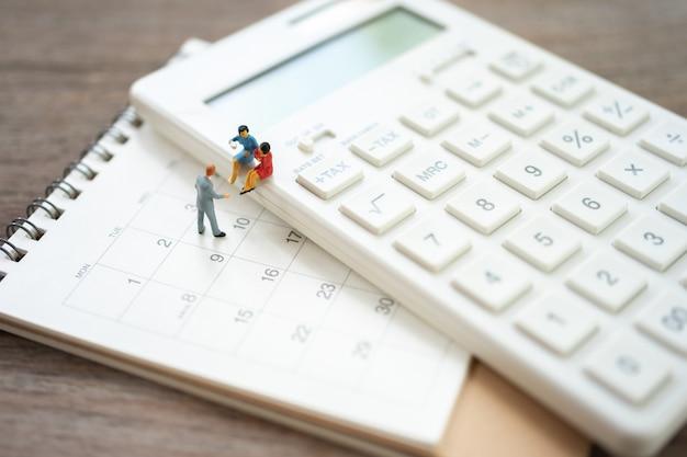 Miniatuurmensen die op witte calculator zitten die als achtergrond bedrijfsconcept gebruiken