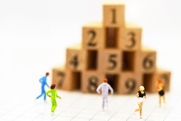 Miniatuurmensen die vóór houten kistnummer lopen.