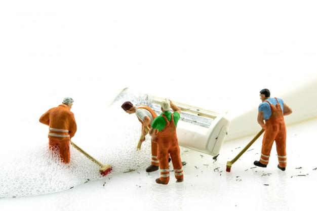 Miniatuurmensen die vuil wit scheerapparaat op witte achtergrond schoonmaken.