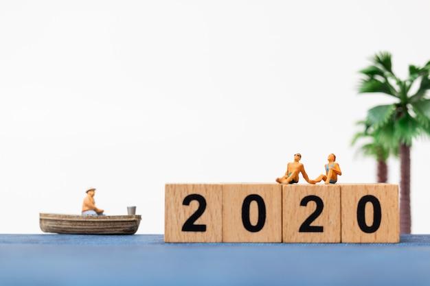 Miniatuurmensen die zwempak ontspannende zitting op houten blok nummer 2020 dragen