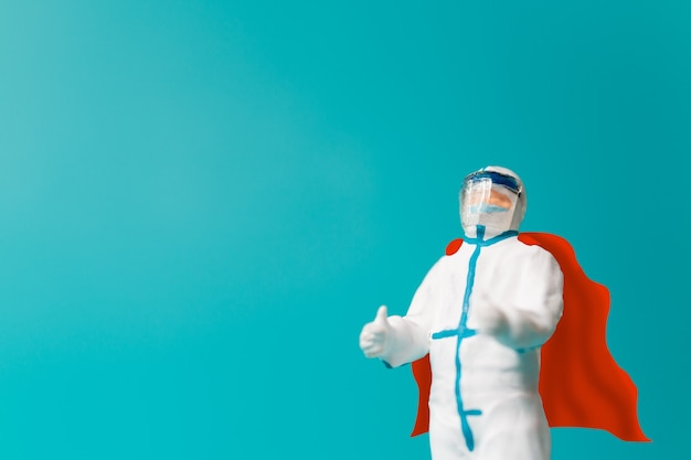 Miniatuurmensen dokter met masker en capeheld, vecht tegen het pandemieconcept van het coronavirus. ziekenhuispersoneel helden concept