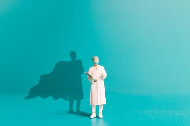 Miniatuurmensen dokter met superheldschaduw op de muur. ziekenhuispersoneel helden concept