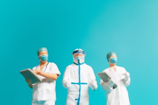 Miniatuurmensen een medisch officier in een beschermend uniform en ruimte voor tekst, close-up