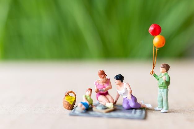 Miniatuurmensen, een mooi stel lesbische dames die zich vermaken in het park met kinderen