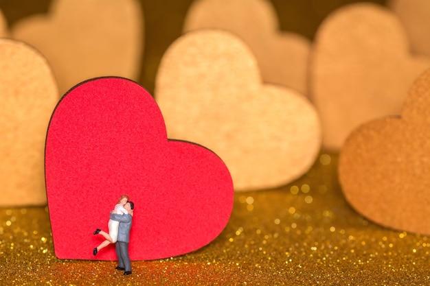 Miniatuurmensen en gouden harten. een liefdevol stel op een stralende achtergrond.