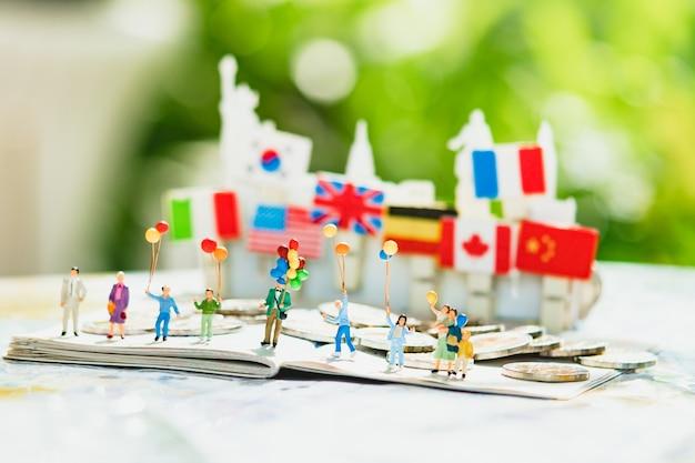Miniatuurmensen, familie met ballon die als achtergrondconcept van de familiedag gebruiken