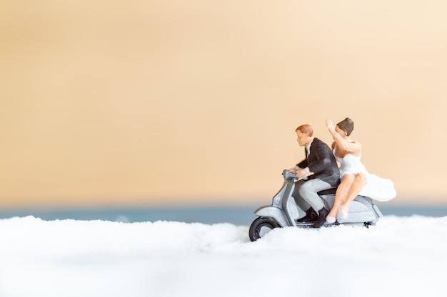 Miniatuurmensen gelukkig huwelijkspaar op wit strand, huwelijksconcept