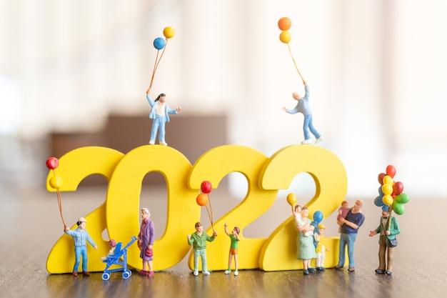 Miniatuurmensen gelukkige familie die ballon houden op wit nummer 2022, gelukkig nieuw jaarconcept