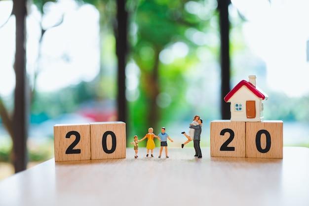 Miniatuurmensen, gelukkige familie die zich met minihuis en houten blok 2020 bevinden die als familie en bezitsconcept gebruiken