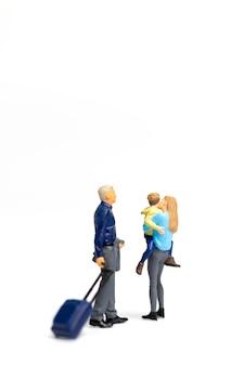 Miniatuurmensen gelukkige familie die zich op witte achtergrond en exemplaarruimte voor tekst bevinden