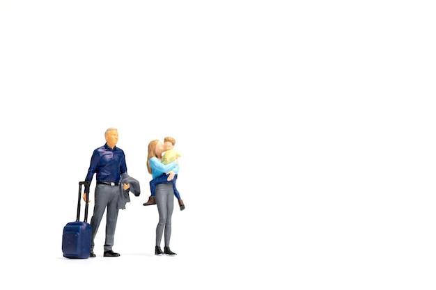 Miniatuurmensen gelukkige familie die zich op witte achtergrond en exemplaarruimte voor tekst bevinden Premium Foto