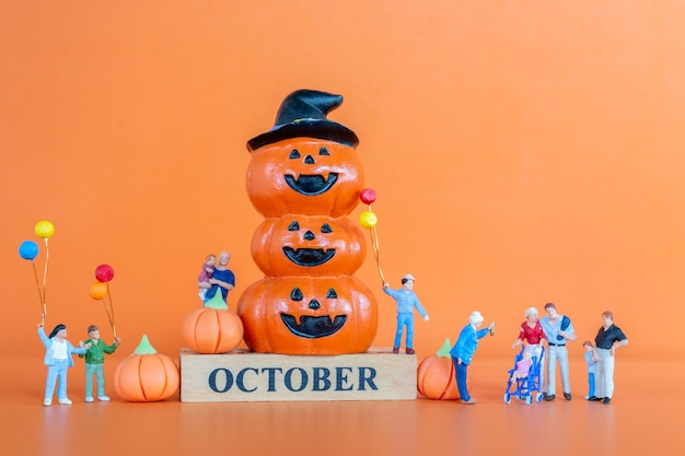 Miniatuurmensen gelukkige familie met pompoen op oranje achtergrond, hello october-concept