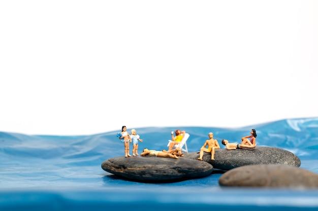 Miniatuurmensen, gelukkige familie zittend op de grote rotsen bij de kust met blauwe zee en witte achtergrond, zomerconcept