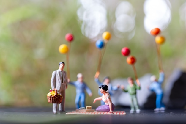 Miniatuurmensen: gelukkige familie zittend op de mat tijdens een picknick in een park