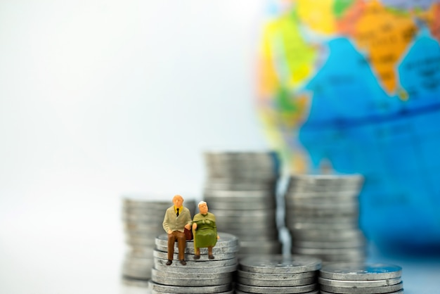 Miniatuurmensen: gelukkige oude mensen die op muntstukkenstapel, pensionering en levensverzekeringsconcept zitten.
