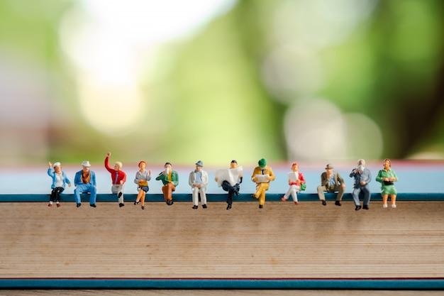 Miniatuurmensen: groep bedrijfsmensen die op een boek zitten.