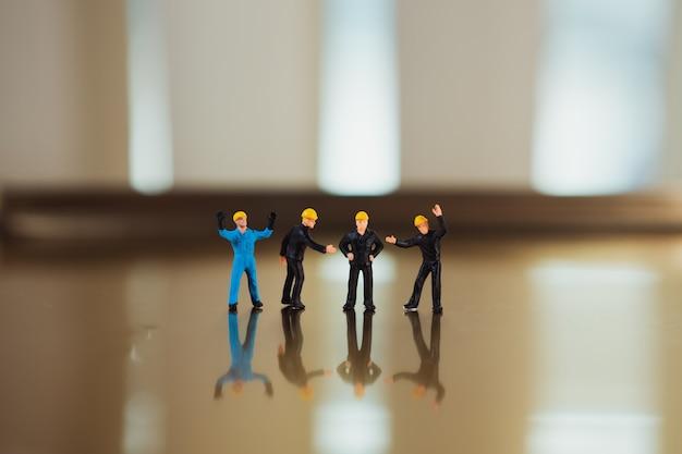 Miniatuurmensen, ingenieursteam bevindende actie die als industrieel concept gebruiken