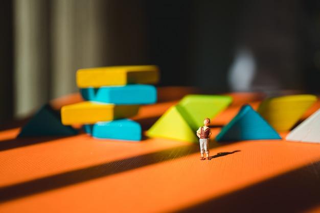 Miniatuurmensen, jonge jongen die zich op tangram-raadselachtergrond bevinden die als concept van de onderwijsvaardigheid gebruiken