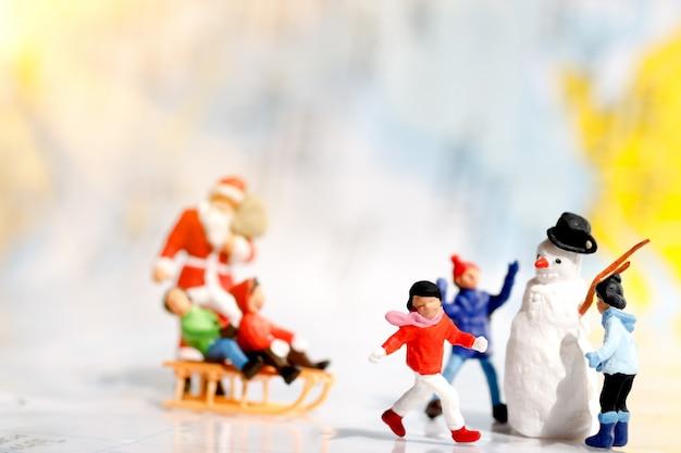 Miniatuurmensen: kerstman en kinderen spelen plezier.