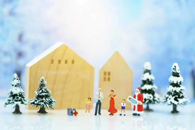 Miniatuurmensen: kerstman met gelukkige familiemensen.
