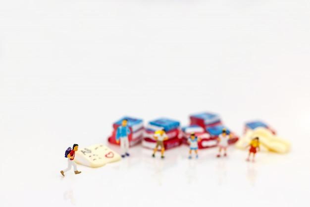 Miniatuurmensen, kinderen die zich met boeken bevinden.