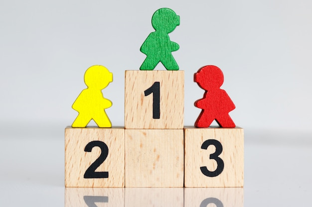 Miniatuurmensen: kleurrijke figuren op houten podium 1,2,3.