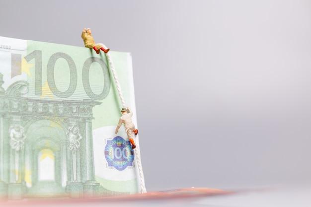 Miniatuurmensen, klimmer klimt op een euro-bankbiljet bedrijfsconcept. Premium Foto