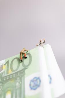 Miniatuurmensen, klimmer klimt op een euro-bankbiljet bedrijfsconcept.