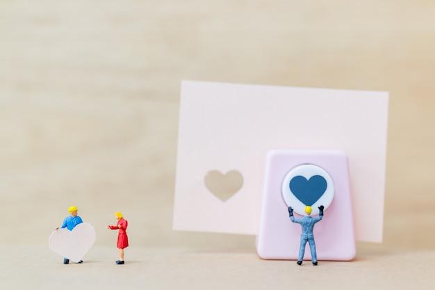 Miniatuurmensen: koppel met papieren hart op houten achtergrond